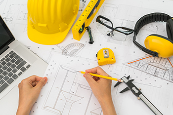 Image with yellow construction hat, measurement tools, safety glasses and blue print